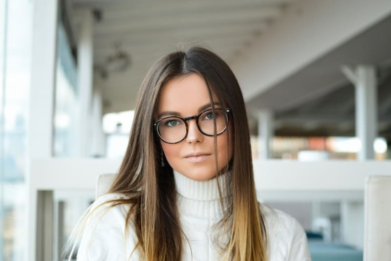 woman with eyeglasses standing near glass window