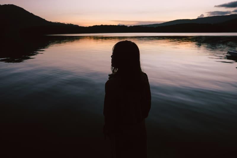 woman standing near lake during sunset