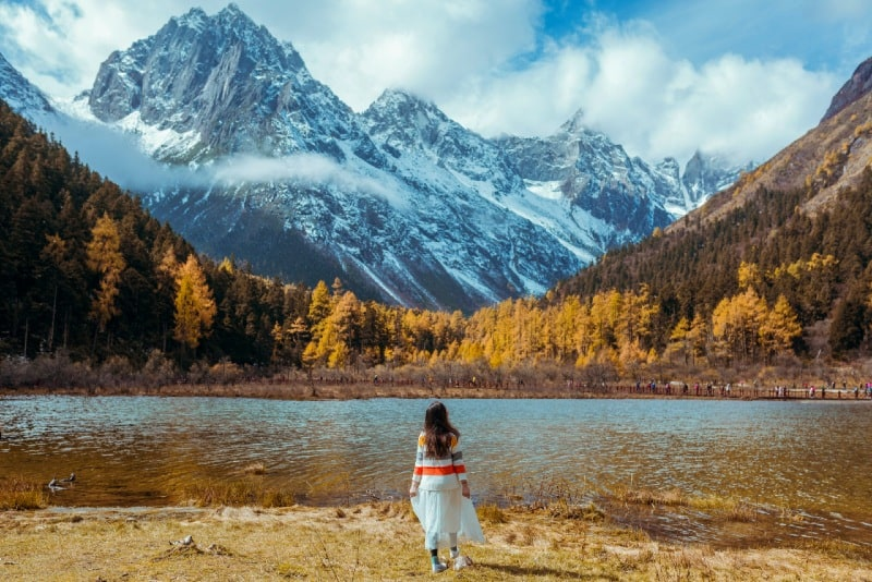 woman standing near lake looking at mountain