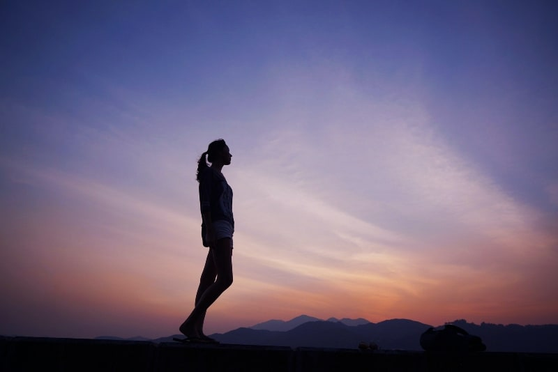 woman standing near mountains during sunset