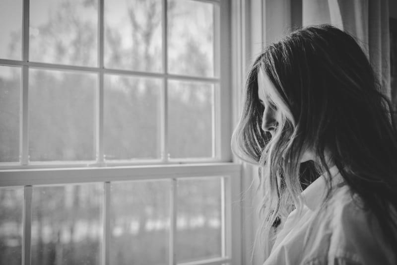 woman in white shirt standing near window