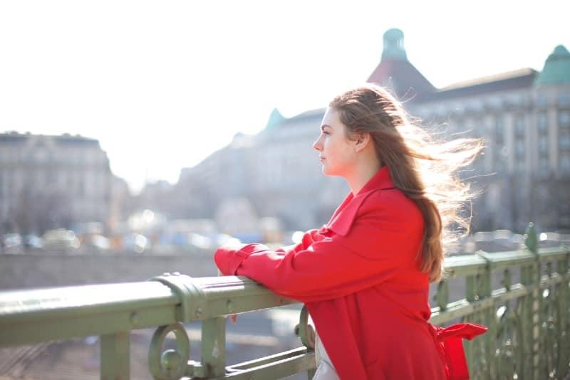 woman in red coat standing on bridge