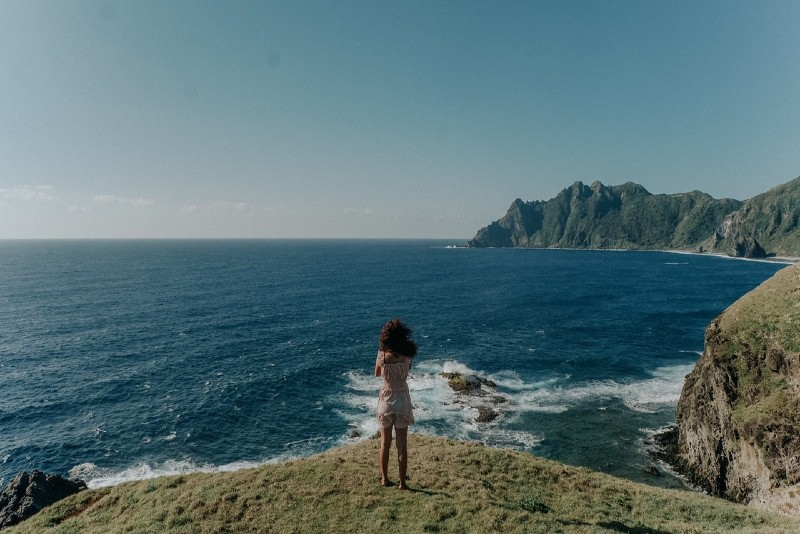 woman in white top standing on cliff looking at sea
