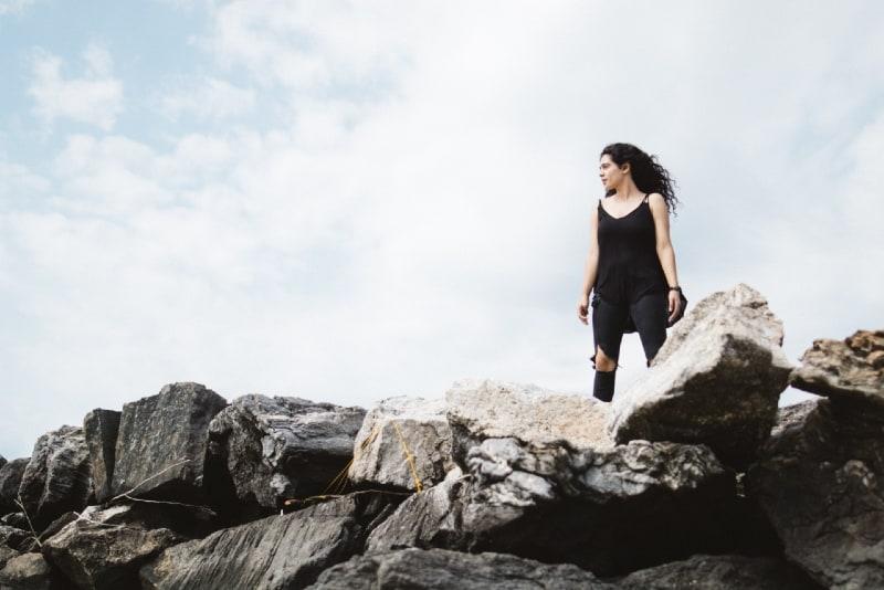 woman in black top standing on rocks