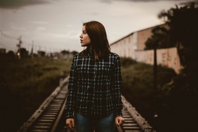 woman in checked shirt standing on train rail track
