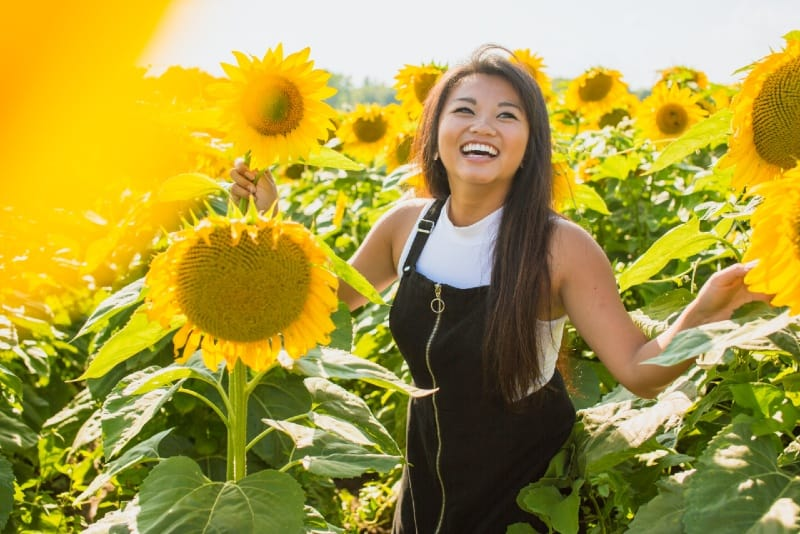 smiling woman standing surrounded sunflowers