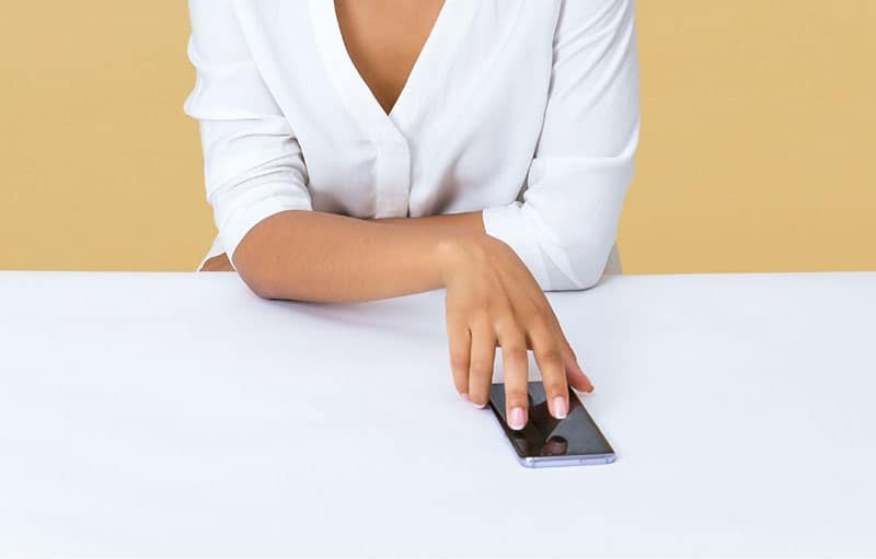 woman touching smartphone laid on the table wearing white top