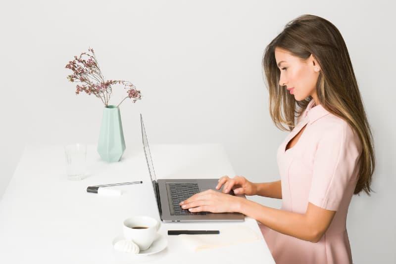 woman in pink dress using laptop