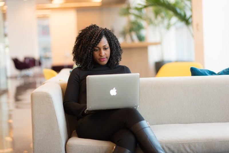 woman in black top using macbook while sitting on couch