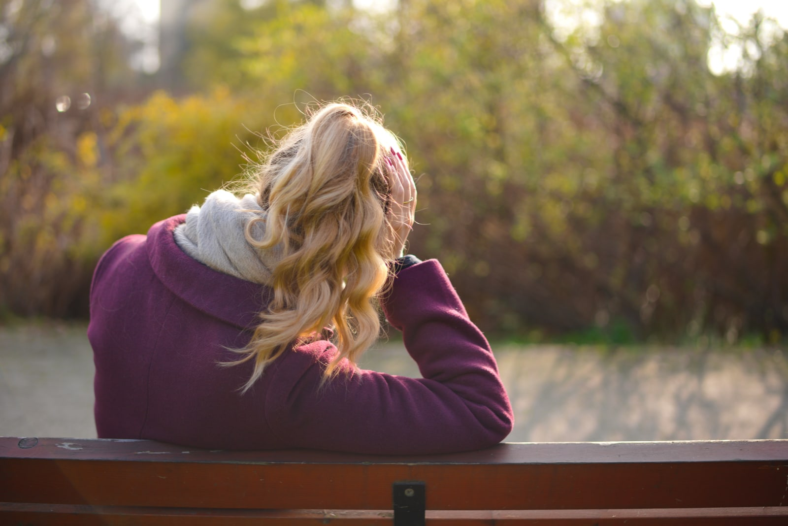 woman with blond hair sitting on a bench in the park