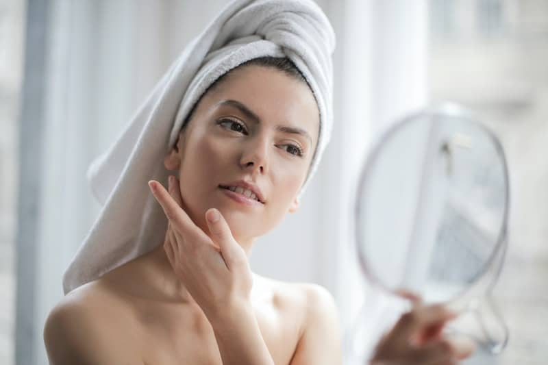 woman with towel on head touching face and facing a small mirror