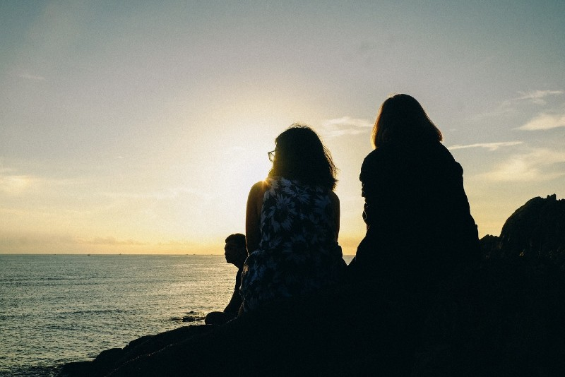two women looking at sea during sunset