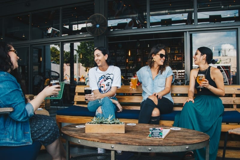 four women sitting on bench holding glasses of beer