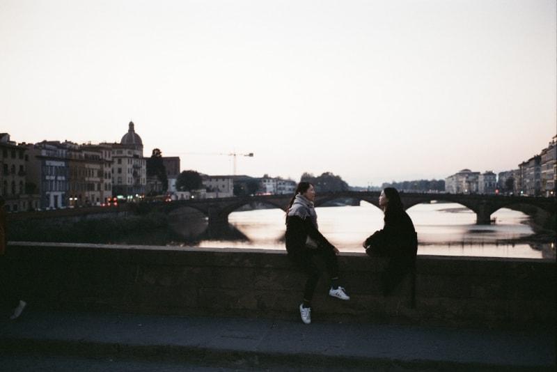 two women sitting on bridge and talking