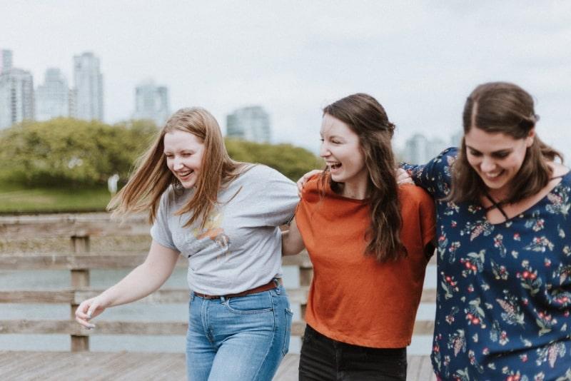 three women walking on dock near high rise buildings