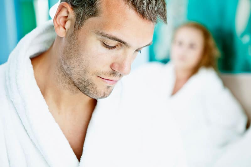 young man in white robe sad with a woman behind him in bed