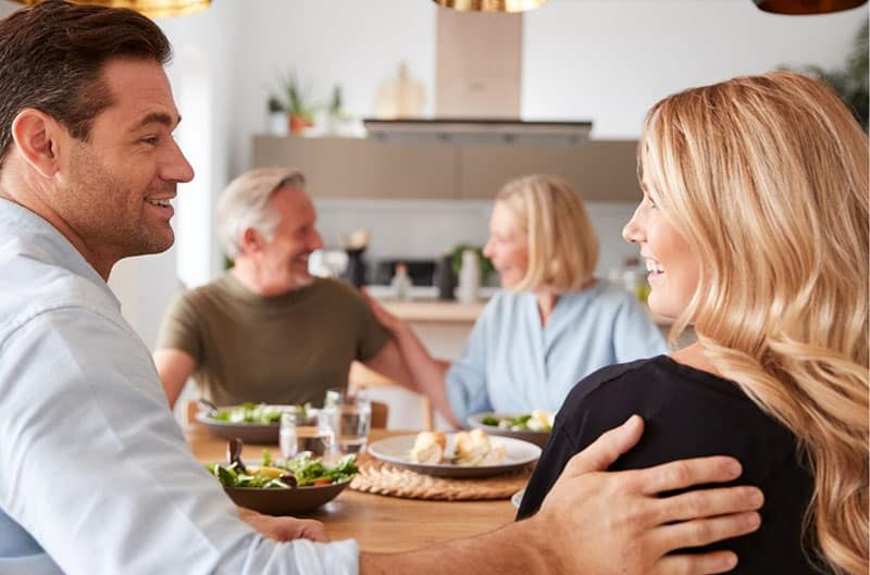 younger couple dining with the older couple seated adjacent to them inside kitchen