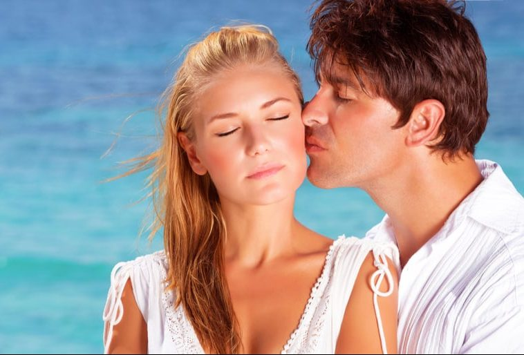woman closing her eyes kissed by a man on her cheeks near a body of water