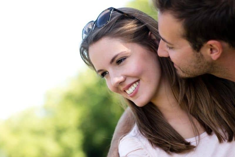 beautiful couple man looking and trying to kiss his wife smiling outdoors