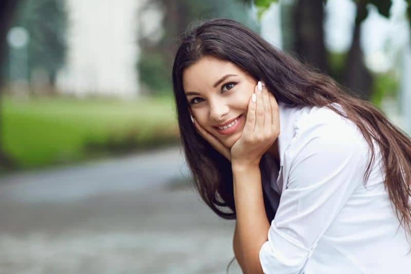 woman smiling outdoors sitting somewhere in the street of the city