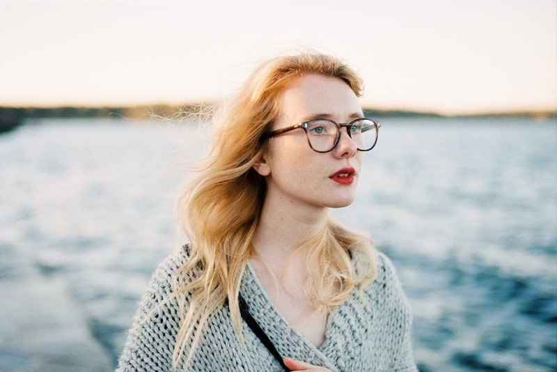 woman with eyeglasses standing near water