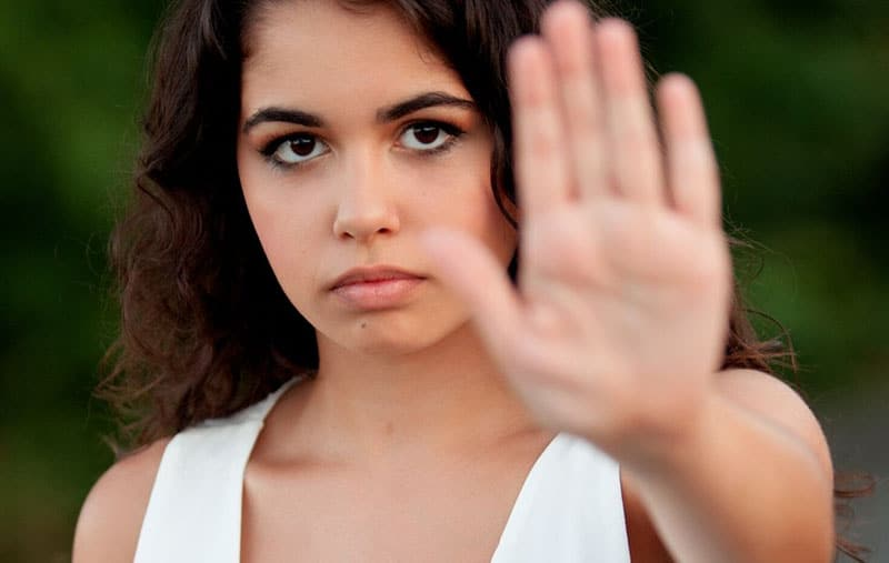 woman i white top making a stop hand gesture