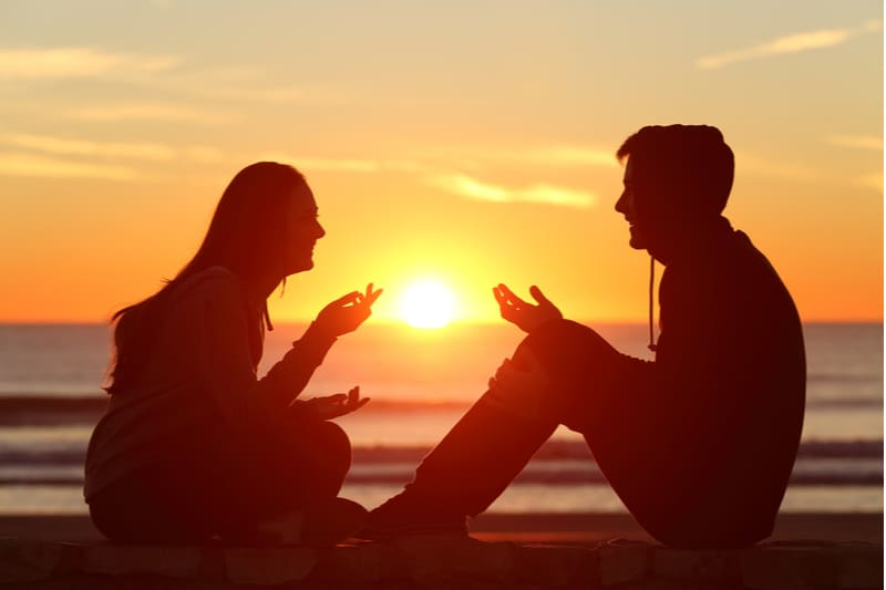 sideview of two friends in full body talking during the sunset near a body of water