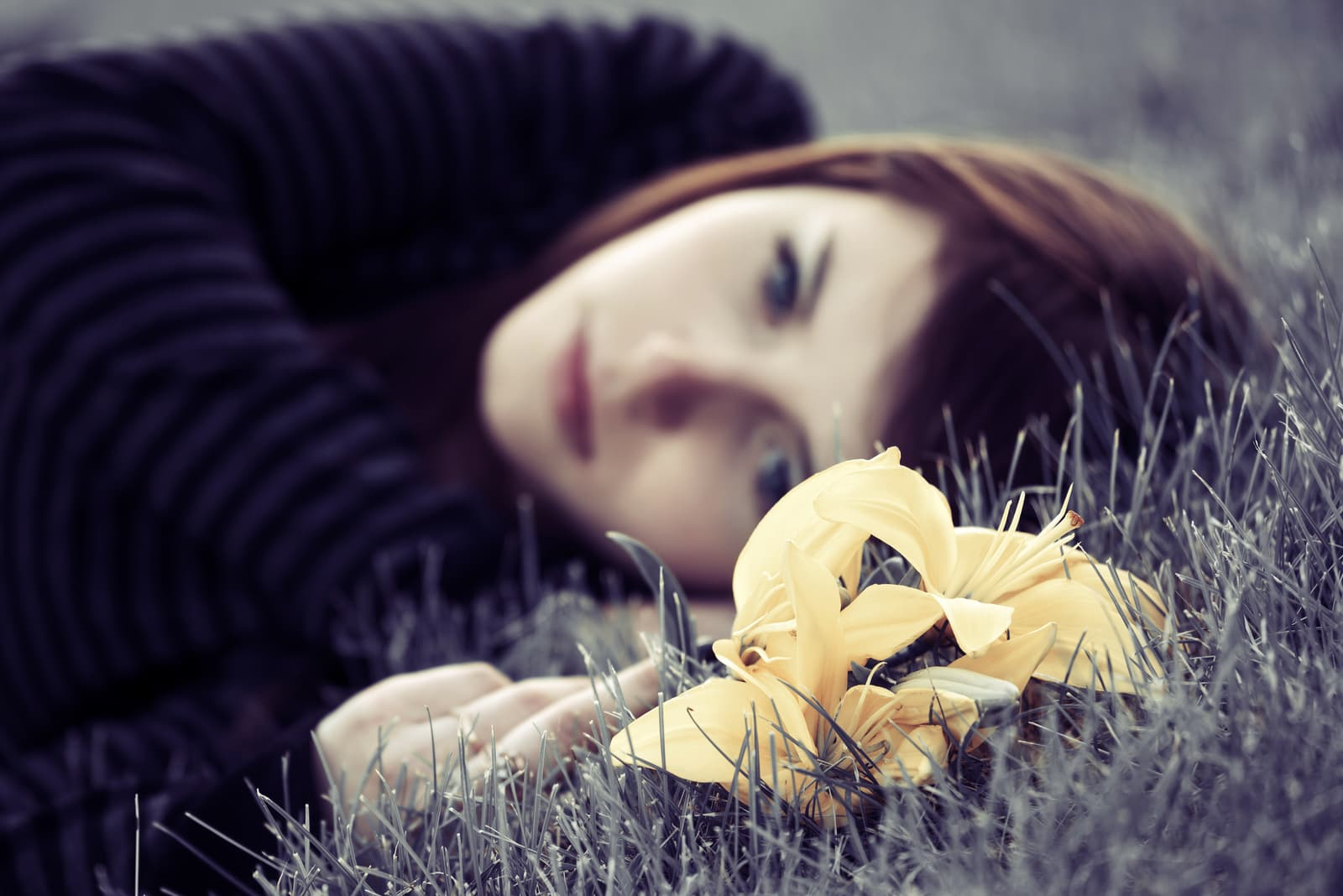 a sad girl lying in the grass with a yellow flower in her hand