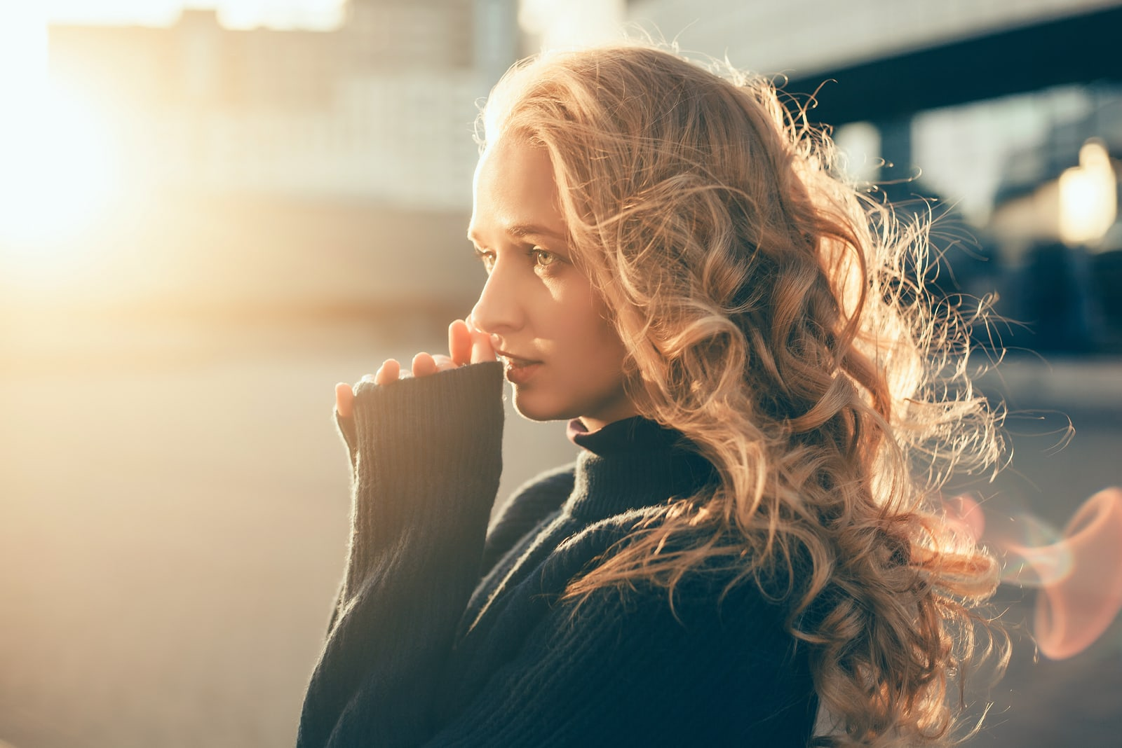 a woman with long blonde hair stands