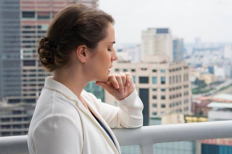 adult business woman closing eyes standing in the rooftop of the building