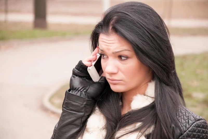angry woman using mobile phone outdoors wearing black jacket