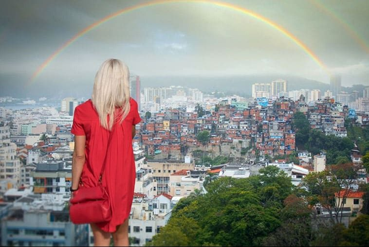 backview of a woman facing a rainbow over the city
