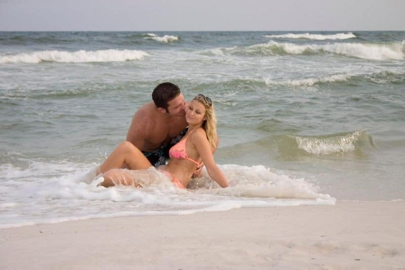 beach lovers enjoying the sea man kissing the woman wearing swimsuit