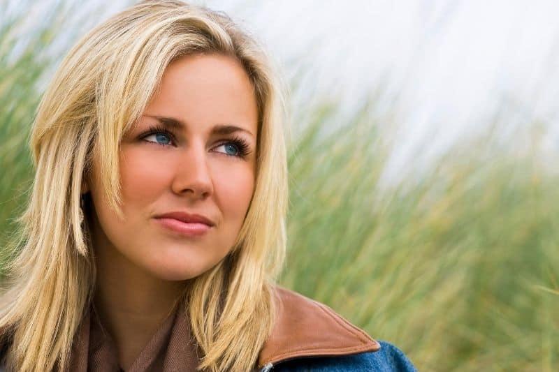 beautiful blonde woman standing near the tall green grasses