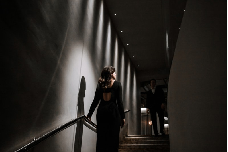 beautiful brunette rises from the stairs in black dress with a man in suit waiting at the top