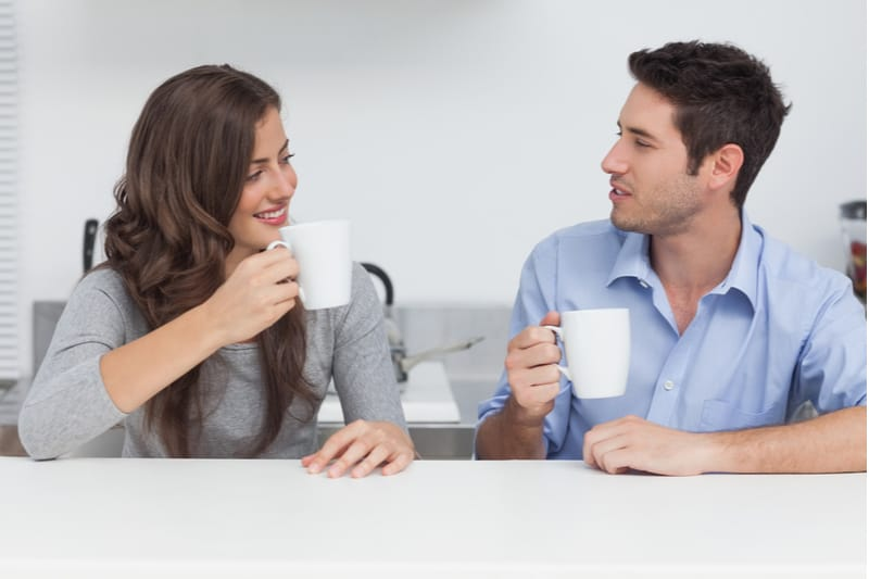 beautiful couple drinking coffee inside the kitchen while talking and sitting