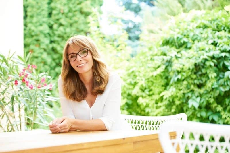 beautiful middle aged woman sitting outdoors with greenery plants nearby