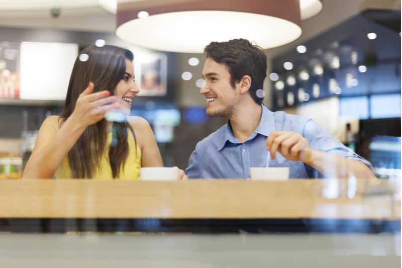 beautiful woman and man talking while having coffee inside a coffee shop