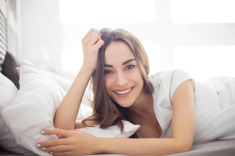 beautiful woman lying on white bedroom smiling