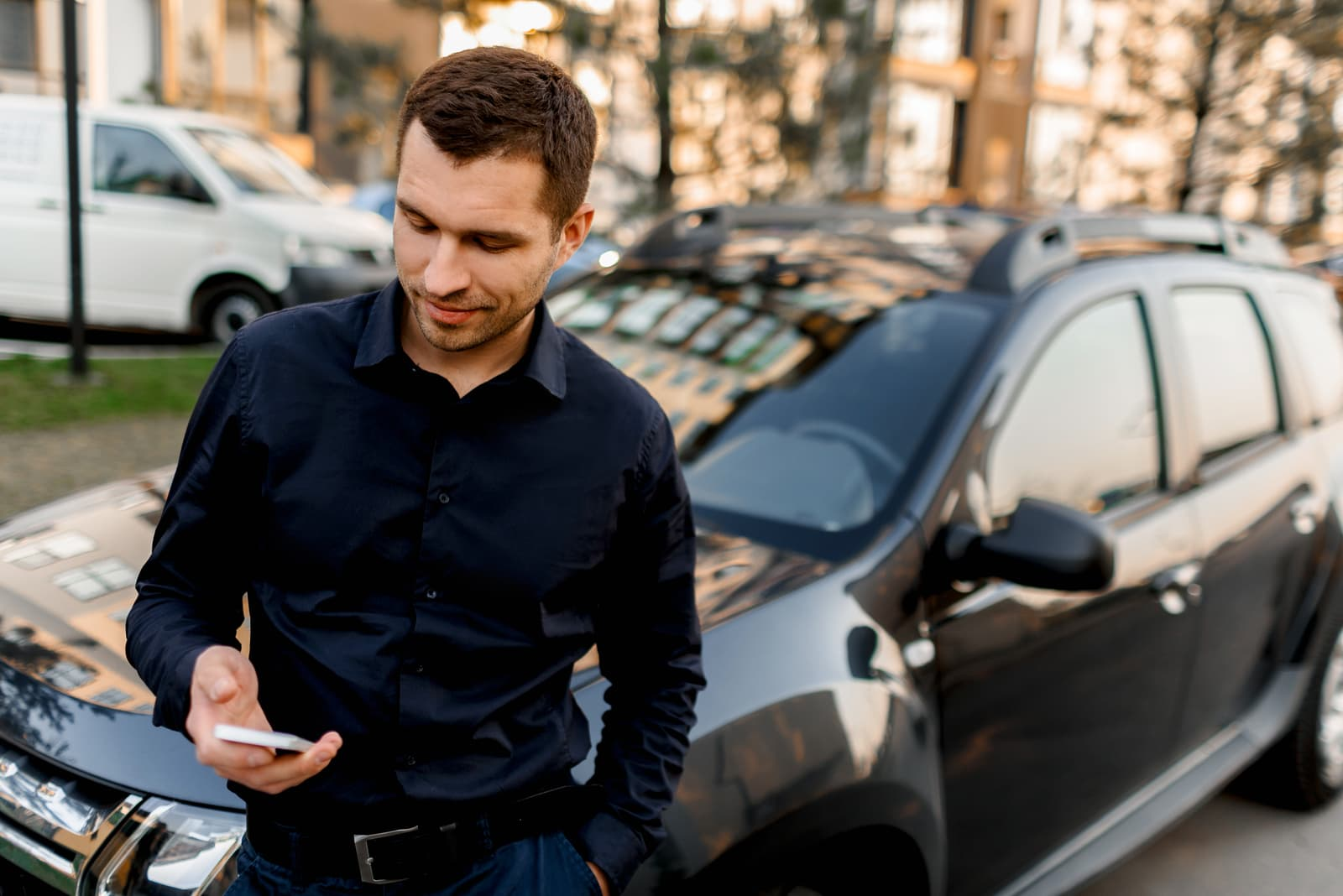 businessman in a dark shirt stands on the street near the car