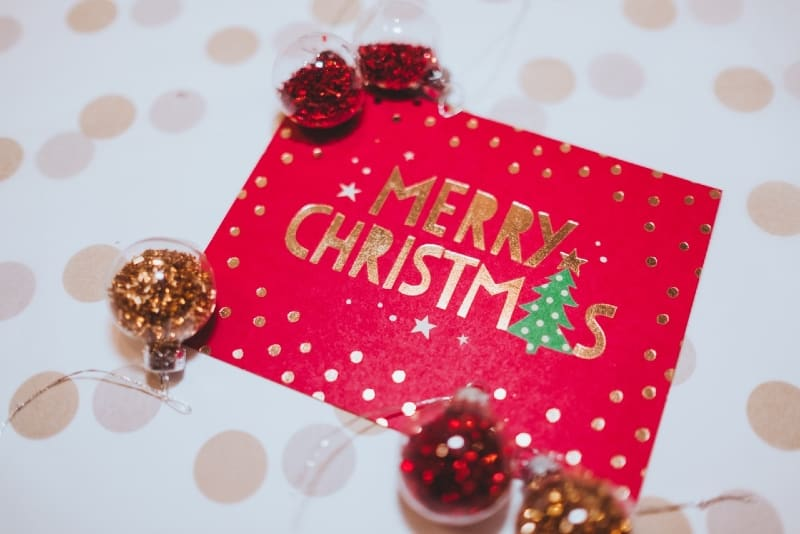 christmas card near red and gold ornaments