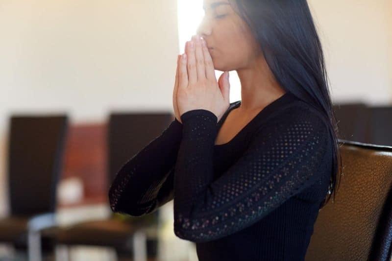 close up of sad woman praying indoors wearing black top