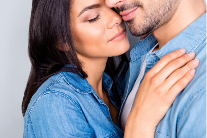 closed cropped portrait of woman smelling and hugging her man
