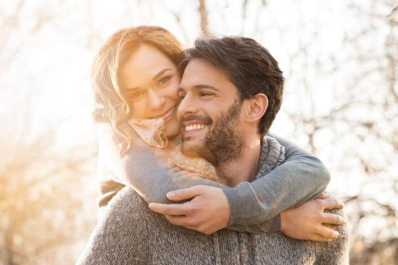 closeup photo of a man giving a piggyback to a woman outdoors
