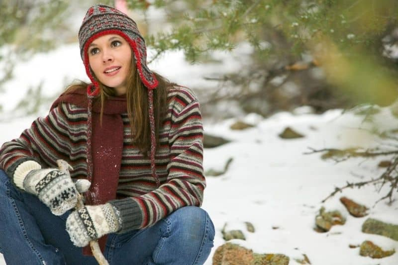 content woman sitting outdoors in a snowy location wearing winter clothes