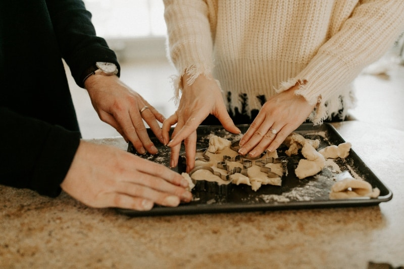 man in black sweater and woman baking christmas cookies