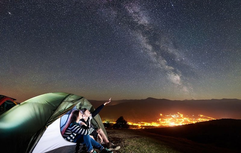 couple camping watching the starry night sky far from the city