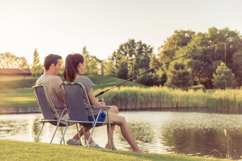 man and woman catching fish while sitting on chairs