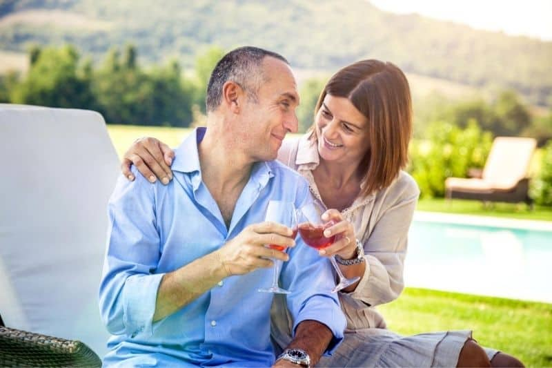 couple celebrating anniversary outdoors clinking wine glasses