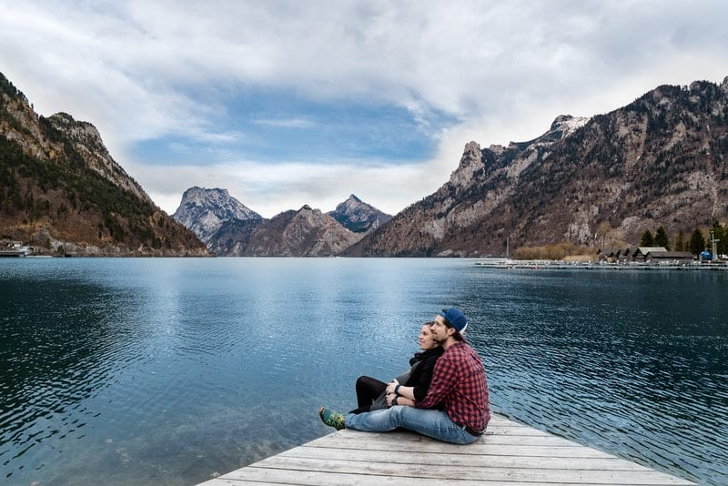 couple cuddling on a wooden platform on a lake with mountains nearby